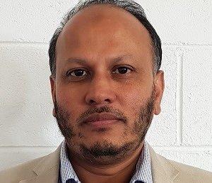 Dr ASM Ashraf Mahmud in front of a white brick wall