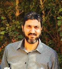 Profile picture of Dr Osama Zaki in a checked shirt in front of green foilage